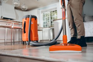 water damage restoration technician vacuuming water in house