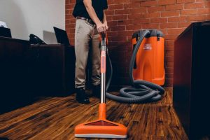 sewage backup technician vacuuming up water in office