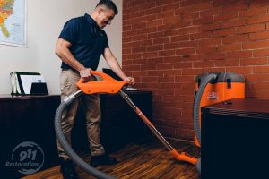 commercial restoration technician vacuuming water from office