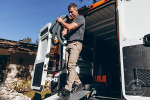 sewage backup cleanup technician taking equipment out of van